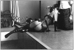woman in black lingerie blowing a man in a suit on a theatrical stage