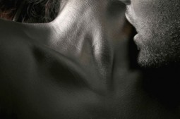 man with his mouth on woman's throat