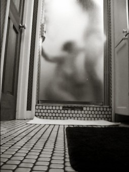 man and woman seen through steamed up shower door with her sucking his cock