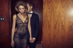 couple in evening attire with her in a stunning see through black dress