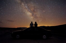 couple silhouetted sitting on car roof looking at night sky