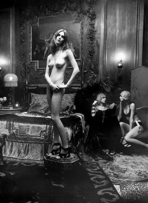 nude girl posing on an ottoman while other nude girls lounge in the background