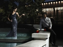 woman in evening dress standing in a fountain pool beckoning to a man in a suit