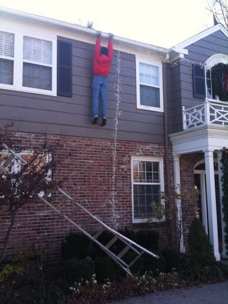 man hanging from roof gutter while trying to string christmas lights