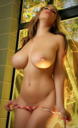 busty brunette girl with pierced nipples standing