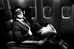 man in suit and mask getting oral sex blowjob from woman in dress in a train car