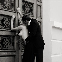 topless woman leaning against ornate carved doors with man in suit fucking her from behind