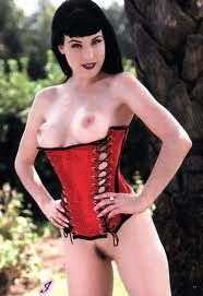 dita von teese posing wearing a red corset showing her bare boobs and pussy
