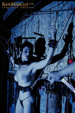 dita von teese restrained against a dungeon wall in a bondage fetish image by ken marcus