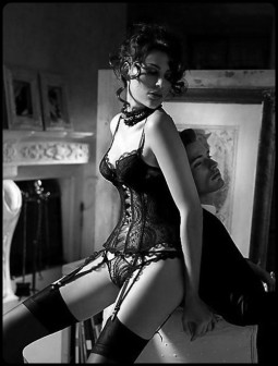 woman in elaborate black lace lingerie leaning on a man in a suit
