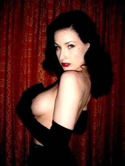 Dita Von Teese holding her beautiful big boobs with black opera gloves on
