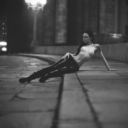 topless brunette in boots and leather pants with pierced nipples reclining on a deserted nightime city street