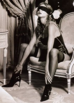 woman in stockings corset and heels having a blindfold tied on her by a man with white gloves