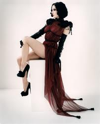 Dita Von Teese posing in black opera gloves, heels and negligee