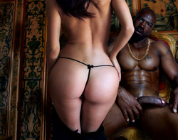 white woman seen from the rear in a string thong approaching a naked black man holding his big black cock and wearing gold chains