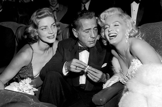 Marilyn Monroe posing with Bogart and Bacall with Bogart eyeing Monroe's cleavage