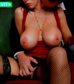 clothed sex with man in suit sitting behind woman in cocktail dress with her boobd pulled out and he is fingering her pussy