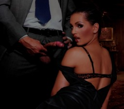 Eve Angel looking back over her shoulder while kneeling in front of man in suit with his cock out