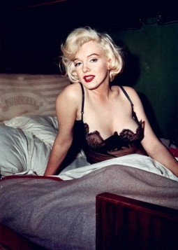 color image of Marilyn Monroe in black lingerie showing beautiful cleavage in bed