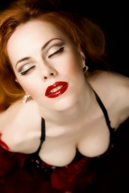 beautiful redhead with red lipstick pale skin and great cleavage in a bustier
