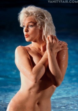 color image of Marilyn Monroe nude by swimming pool with arms crossed over her breasts