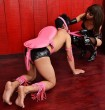 submissive man on hands and knees outfitted with pink riding saddle while femdom pulls on a leash around his neck