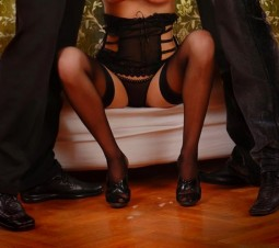 clothed sex image of woman in black lingerie sitting between two standing men in suits and cum on the floor