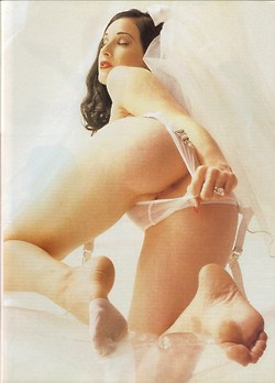 Image from the rear of Dita Von Teese pulling her panties aside to show her anus and pussy
