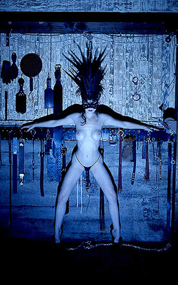 fetish image of Dita Von Teese in a dungeon setting naked but for g-string, heels, mask, and a weird headdress