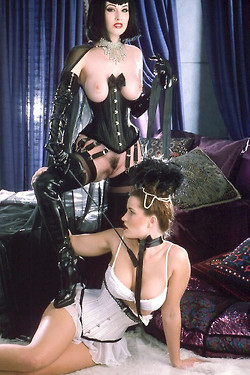 Dita wearing black boots and corset showing bare pussy and boobs playing dominatrix over a blonde in white lingerie
