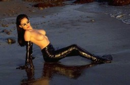 Dita Von Teese sitting topless on a beach wearing black latex opera gloves and latex pants