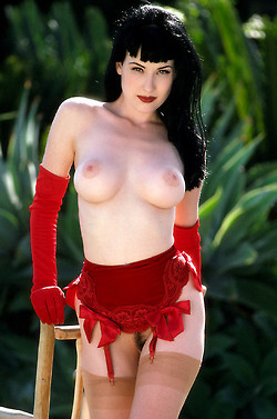 Diata Von Teese in rich red garter betl, stockings and gloves showing her bare tits and pussy with landing strip