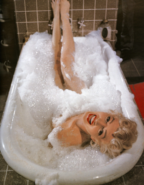 Marilyn Monroe nude and smiling at the camera from a bubble bath