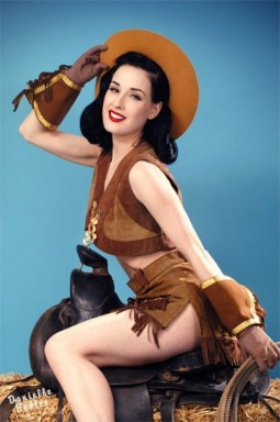 Dita Von Teese in a cowgirl outfit riding a saddle for a burlesque routine