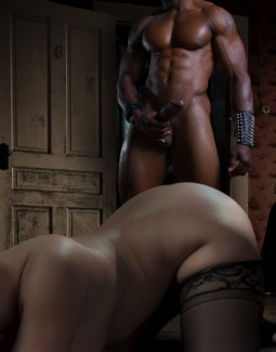 white woman kneeling ass up whil;e muscular black man with big cock and wearing studded gauntletsapproaches from the rear