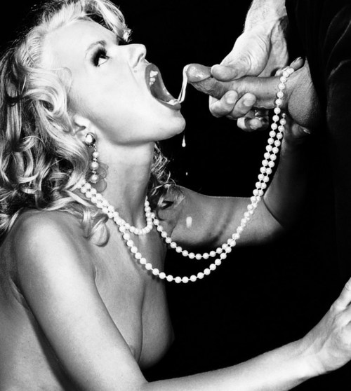 blonde wearing only a long string of pearls taking a cumshot to her mouth from a man in a suit