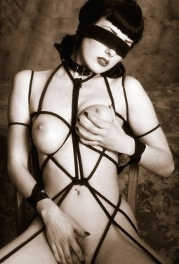 Dita Von Teese in a fetish image blindfolded and tied in rope bondage