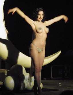 Dita Von Teese in only pasties and g-string with an ivory elephant tusk in burlesque routine