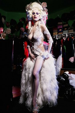 Dita Von Teese in an elaborate burlesque costume with feathers and rinestones and crystals