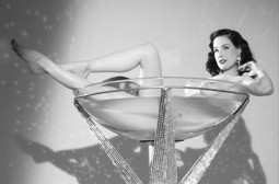 Dita Von Teese reclining in her trademark martini glass in her burlesque routine