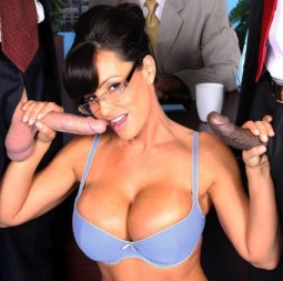 porn star Lisa Ann in a blue bra and glasses looking like Sarah Palin and kneeling between two men in suits with their cocks out