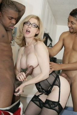 Nina Hartley in black lingerie and glasses in interracial threesome fucking one black man and giving another a handjob