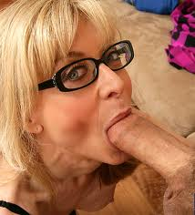Nina Hartley wearing black frame glasses looking at camera while giving a blow job