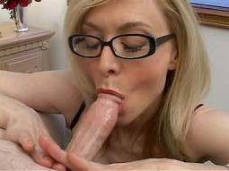 Nina Hartley wearing glasses and focused on sucking a long fat cock