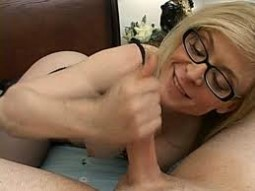 Nina Hartley wearing glasses jerking off masturbating a cock while smiling