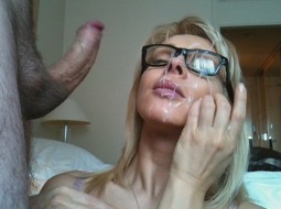 girl wearing glasses wiping her face after a messy cumshot facial