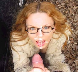 clothed sex redhead in glasses taking a cumshot on her nose, face, and glasses during a blowjob