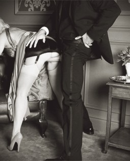 couple having clothed sex in their formal wear with her bent over a chair and him entering from behind