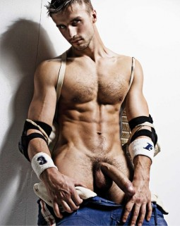 naked man with his pants pulled down showing off his big cock and wearing elbow pads, straps and wrist bands