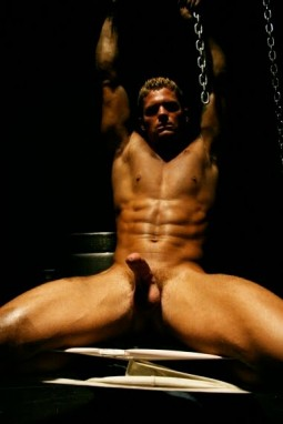 buff nude man with erect cock sitting in a chair with arms over his head
